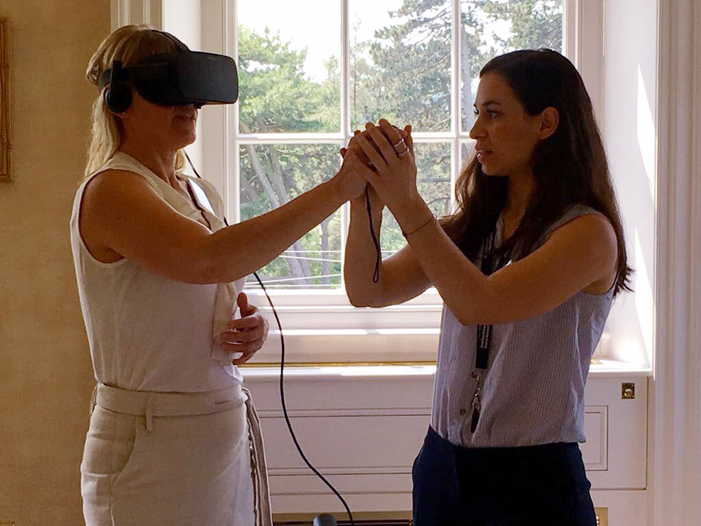 Woman wearing VR headset, being helped by second woman.